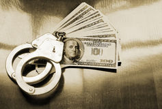 Stack of money and handcuffs. On table Royalty Free Stock Photography