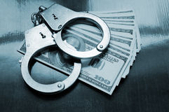 Stack of money and handcuffs. On table Royalty Free Stock Images