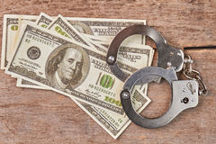 Stack of money and handcuffs on table. Law punishment of criminal Stock Photography
