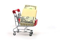 Stack of money in a shopping cart isolated on white background stock image