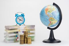 A stack of money worth hours, a stack of coins, a globe royalty free stock images