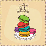 Stack of multi-colored French cookies macaron. Stack of multi-colored French cookies, known as the macaron, lie on lacy napkin. Beige background and ornate Royalty Free Stock Photo