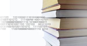 Stack of multicolored books. Old textbooks stacked on each other. Online education technology concept. E-learning. Training skill courses. Binary code data royalty free stock images