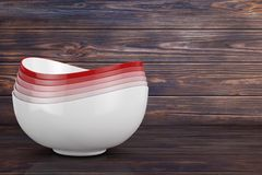 Stack of Multicolored Ceramic Food Bowls. 3d Rendering. Stack of Multicolored Ceramic Food Bowls on a wooden plank background. 3d Rendering royalty free illustration