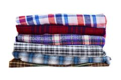 Stack of multicolored checkered winter clothes isolated on white background stock photo