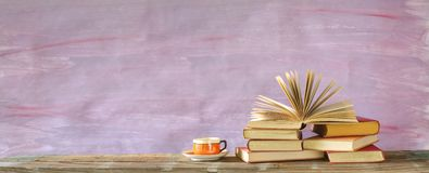 Stack of multicolored hardback books and an opened book, reading, education, literature royalty free stock images