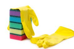 A stack of multicolored sponges and yellow rubber gloves for wet cleaning and dish washing on a white background Stock Images