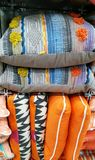 Stack of multicoloured cushions. Retail. Orange blue and yellow colored cushions for sale Stock Images