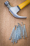 Stack of nails and claw hammer on wooden board Royalty Free Stock Photography