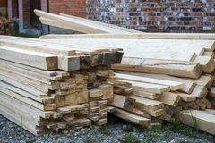 Stack of natural brown uneven rough wooden boards on building site. Industrial timber for carpentry, building, repairing and. Furniture, lumber material for stock photos