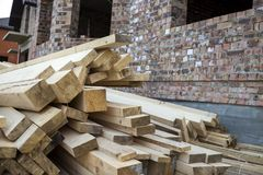 Stack of natural brown uneven rough wooden boards on building site. Industrial timber for carpentry, building, repairing and. Furniture, lumber material for stock photography