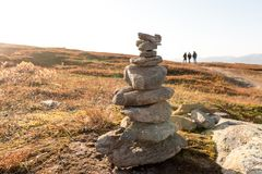 Stack of natural irregular stones in grassland with people in ba Stock Image