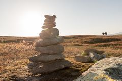 Stack of natural irregular stones in grassland with people in ba Stock Images