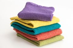 Stack of neatly folded colorful kitchen towels. On white background Stock Images