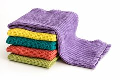 Stack of neatly folded colorful kitchen towels. On white background Royalty Free Stock Image