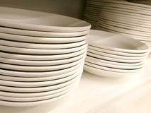 Stack of new clean white plain plates and bowls on the shelf royalty free stock photography