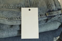 A stack of new jeans with paper price tag mockup. Sale clothing concept. A stack of new jeans with white paper price tag mockup. Sale clothing concept stock image