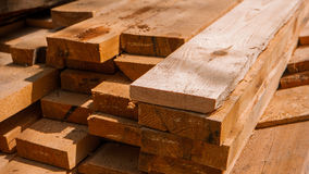 Stack of new wooden studs at a lumber yard warm color tone selective focus. Stock Images