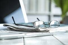 Stack of  newspaper with eyeglasses on laptop Stock Images