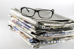 Stack of newspaper with glasses royalty free stock photos