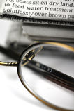 Stack of newspapers. A pair of glasses in front of some newspapers Stock Photography