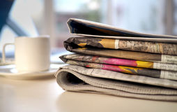 Stack of newspapers with coffee cup and computer Stock Images