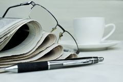 Stack of newspapers with coffee cup on white background. stock photography