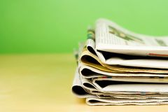Stack of newspapers in color on green background. Stack of newspapers in color lying on table on green background Stock Photography