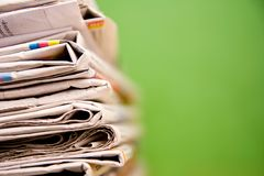 Stack of newspapers in color on green background Royalty Free Stock Image