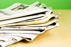 Stack of newspapers in color on green background. Stack of newspapers in color lying on table on green background Royalty Free Stock Photography