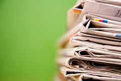 Stack of newspapers in color on green background Royalty Free Stock Images