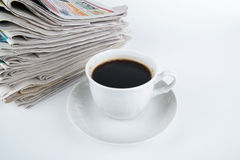 Stack of newspapers with cup of coffee close-up Stock Images