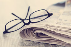 Stack of newspapers and eyeglasses Royalty Free Stock Images