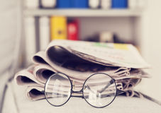 Stack of newspapers and eyeglasses Stock Photography