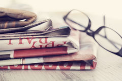 Stack of newspapers and eyeglasses Stock Images