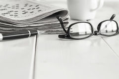 Stack of newspapers with eyeglasses and coffee Stock Photos