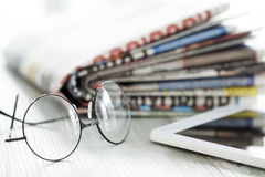 Stack of newspapers, eyeglasses and digital tablet Royalty Free Stock Images
