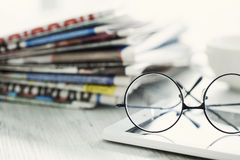 Stack of newspapers, eyeglasses and digital tablet Royalty Free Stock Image