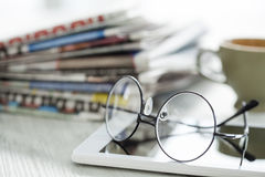 Stack of newspapers, eyeglasses and digital tablet Royalty Free Stock Photography