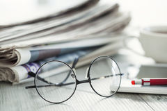 Stack of newspapers, eyeglasses and digital tablet Stock Photos