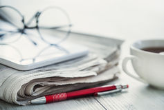 Stack of newspapers, eyeglasses and digital tablet Stock Photography
