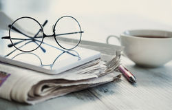 Stack of newspapers, eyeglasses and digital tablet Royalty Free Stock Photos