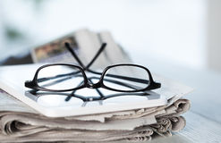 Stack of newspapers, eyeglasses and digital tablet Stock Image