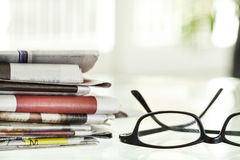 Stack of newspapers and eyeglasses Royalty Free Stock Photography