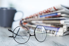 Stack of newspapers, eyeglasses on table Royalty Free Stock Photo