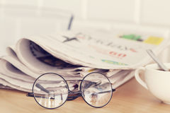 Stack of newspapers, eyeglasses on table Stock Photos