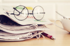Stack of newspapers, eyeglasses on table Royalty Free Stock Photography