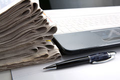 Stack of newspapers and keyboard close-up Stock Photo