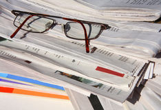 A stack of newspapers and magazines. Reading newspapers and magazines with eyeglasses Royalty Free Stock Images