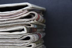 Stack of newspapers. Stack or pile of newspapers on black background closeup Royalty Free Stock Photo